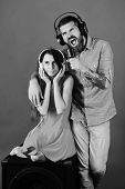 Couple Listening To Music. Party And Music Concept. Man With Beard And Girl Sit On Black Boombox On  poster