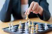 Close Up Shot Hand Of Business Woman Moving Golden Chess To Defeat A Silver King Chess On White And  poster