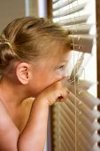 Little Girl Looking Out The Window Through The Blinds. poster