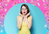 Portrait Of Beautiful Surprised Young Woman In Glasses On The Wonderful Blue Studio Background With  poster
