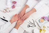 Cropped Image Of Manicurist Looking At Hands Of Woman At Table With Flowers, Towels, Nail Polishes,  poster