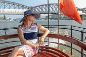A Pretty Smiling Elegant Woman In A Hat, Middle Aged, Sitting On A Ferry Bench, Enjoying A Sightseei poster
