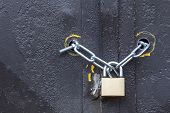 Padlock With Chain On The Iron Gate. Black Background. The Concept Protects Reliably. poster