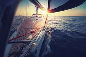 Sunset at the Sailboat deck while cruising / sailing at opened sea. Yacht with full sails up at the  poster