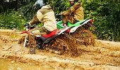 Motocross Racers Racing On The Off-road Circuit Mud Flying Through Air. Motorbike Rides Through The  poster