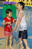 image of summer fun  - A girl iand a boy are plyaing with water fountain in Park California - JPG