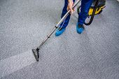 Photo Of Janitor Cleaning Carpet With Vacuum Cleaner poster