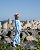 little girl in tracksuit stand on rocks near concrete block