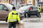 Policemans In Reflective Vests With Stop Signs Organizing Traffic At Crossroad poster