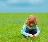 Cute little girl picking flowers on the meadow on cloudy spring day