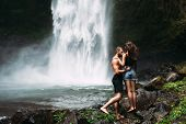 A Man Of Athletic Build Kisses A Beautiful Girl At The Waterfall. Honeymoon Trip. Declaration Of Lov poster
