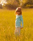 Cute happy girl walking in the field of wheat on sunny spring day