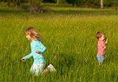 Brother and sister playing on the meadow on sunny summer day