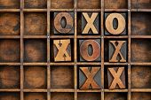 tic-tac-toe or noughts and crosses game - vintage letterpress printing block X and O in wooden grung