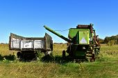 Posterior Image Of An Old Discarded Truck With A Grain Box And Huge Combine With Extended Auger Brin poster