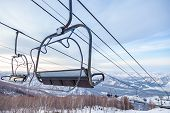 A Ski Lift Chair Cableway With A Booth Suspended On A Cable In Which Sits People With Skis And Snowb poster