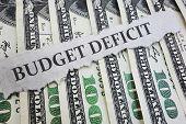 Budget Deficit News Headline On Hundred Dollar Bills  -- Government Spending Concept poster