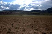 Vast Steppe With Shallow Vegetation At The Foot Of The Hill. poster