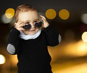 stock photo of little boy  - portrait of a funny kid wearing heart sunglasses at a city by night - JPG