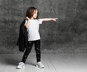 Small Girl In Black And White Rock Star Style Casual Clothing And White Sneakers Standing And Pointi poster