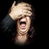 Dark portrait of a woman being abused and silenced by a man who is covering her eyes with his hand while she screams