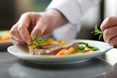stock photo of restaurant  - Chef decorating a dish in restaurant kitchen - JPG