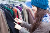 Woman Choosing Clothes At Flea Market.