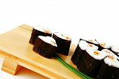 rolls of sushi on wood stand over white