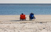 stock photo of snowbird  - Two people resting in orange and blue beach chairs - JPG
