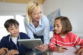 stock photo of schoolgirls  - Teacher in class with kids using electronic tablet - JPG