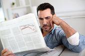 Mann zu Hause lesen Hiobsbotschaften auf Zeitung