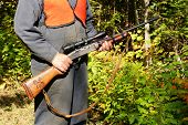 stock photo of hunt-shotgun  - Real man wearing bright orange vest going moose hunting with rifle carving on handle in the forest during fall or autumn in northern canada - JPG