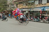 Women On A Bicycle With Colorful Balloons On The Street. Hanoi. Vietnam.