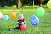 Little boy is playing with colorful balloons, which is tied to a rope in the park