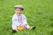 stock photo of national costume  - The little boy in the russian national costume playing with ball on the grass - JPG