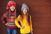 image of little sister  - Cute little girls wearing knit winter clothes posing over wooden background - JPG