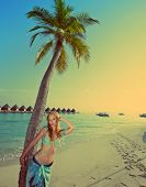 Young beautiful woman stands near palm tree Maldiveswith a retro effect