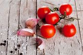 cherry tomatoes, garlic, peppercorns and salt on rustic wooden background
