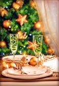 Christmas table setting, festive dinner still life and beautiful decorated Xmas tree at home, New Ye