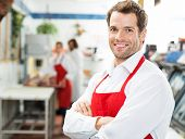 Portrait of happy male butcher standing arms crossed at store with colleagues working in background