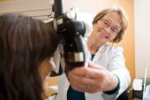 Happy senior female optometrist adjusting phoropter for patient in eye clinic