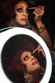 image of cross-dressing  - Cross dressing man putting on makeup at a mirror - JPG