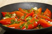 Roasted red bell peppers in a round pan.