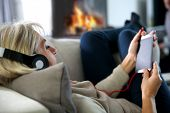 Senior woman relaxing in sofa with music headset on