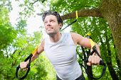 stock photo of suspension  - man exercising with suspension trainer sling in City Park under summer trees for sport fitness - JPG