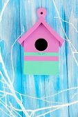 Decorative nesting box  with color branches, on color wooden  background