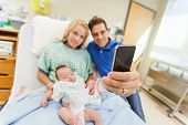 Man with woman and newborn babygirl taking selfportrait through cell phone in hospital room