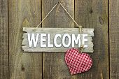 Wood welcome sign with red heart hanging on rustic door
