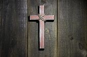 Spotlight on wood cross hanging on rustic wooden background