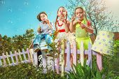 Cute little girls with boy are blowing a soap bubble